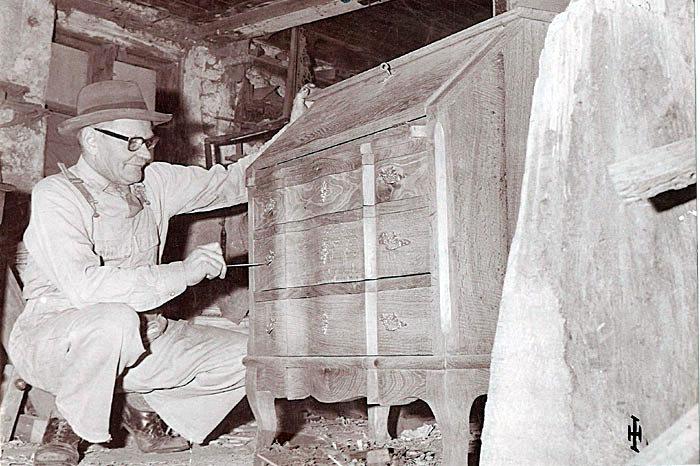 Karetmager Laurits Sørensen den 20. oktober 1962. Værkstedet, som fremstår uisoleret med rå vægge, lå på Ajstrupvej 16 i Malling. Laurits Sørensen specialiserede sig især i finere snedkeri fx det chartol, som ses på billedet. Prisen var kr. 500. Værkstedet ophørte i 1970.
