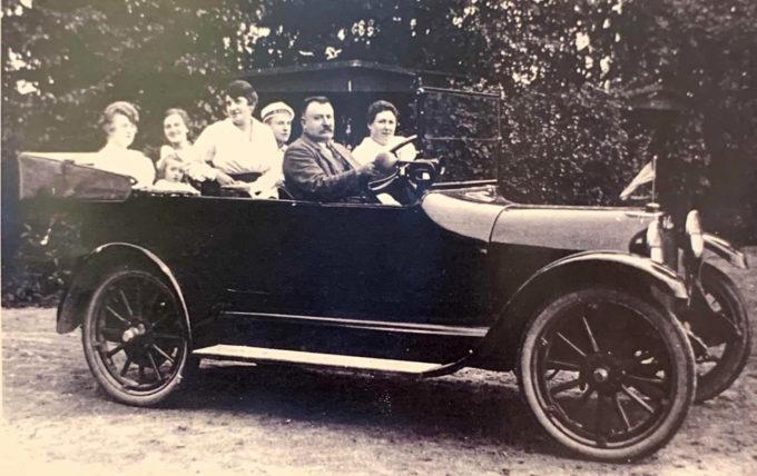 Niels P. Pedersen i en Studebaker omkring 1920. Bilen har rattet i højre side og er pyntet med amerikansk flag.