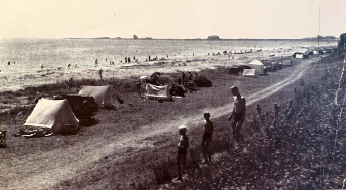 Badegæster samt telte på stranden