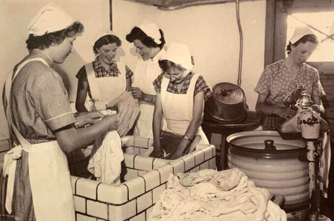 4 elever i skolens vaskeri. Lærerinden giver gode råd til at få skjorteflippen ren